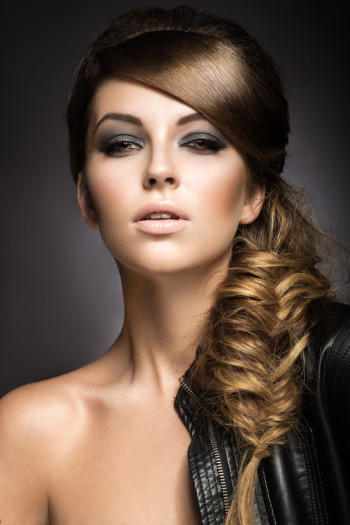 Beautiful girl with bright make-up, perfect skin and hairstyle as a braid.Picture taken in the studio on a gray background